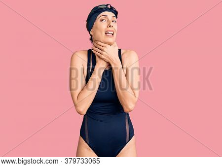Young beautiful hispanic woman wearing swimwear and swimmer glasses shouting and suffocate because painful strangle. health problem. asphyxiate and suicide concept.