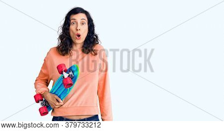 Young beautiful hispanic woman holding skate scared and amazed with open mouth for surprise, disbelief face