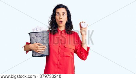 Young beautiful hispanic woman holding paper bin full of crumpled papers scared and amazed with open mouth for surprise, disbelief face