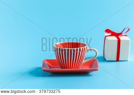 Tea Pair: A Mug On A Saucer And A White Gift Box Tied With A Red Ribbon In The Background. The Conce