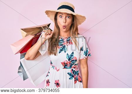 Middle age hispanic woman wearing hat holding shopping bags scared and amazed with open mouth for surprise, disbelief face