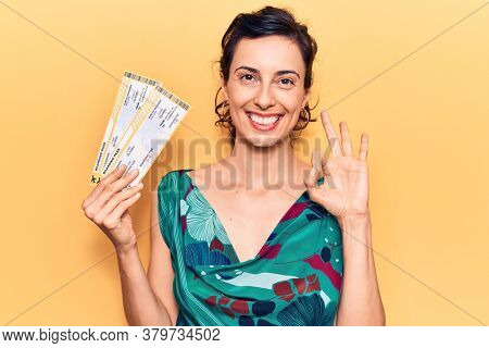 Young beautiful hispanic woman holding boarding pass doing ok sign with fingers, smiling friendly gesturing excellent symbol
