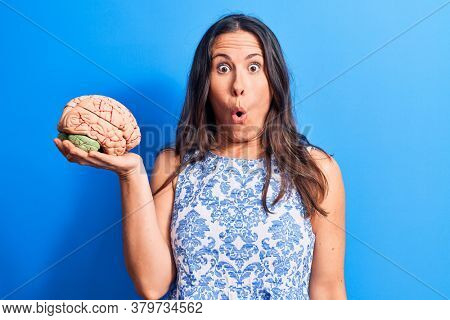 Young beautiful brunette woman asking for care memory holding brain over blue background scared and amazed with open mouth for surprise, disbelief face