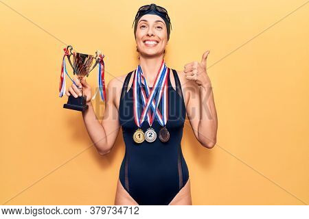 Young beautiful hispanic woman wearing swimmer swimwear and winner medals holding trophy smiling happy and positive, thumb up doing excellent and approval sign