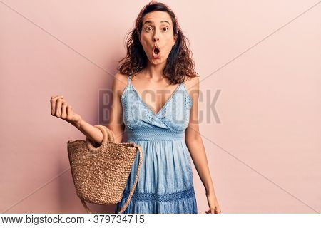 Young beautiful hispanic woman wearing casual clothes holding bag scared and amazed with open mouth for surprise, disbelief face