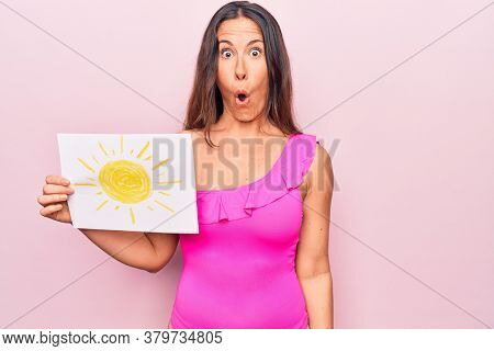 Young beautiful brunette woman wearing pink swimwear holding paper with sun draw scared and amazed with open mouth for surprise, disbelief face
