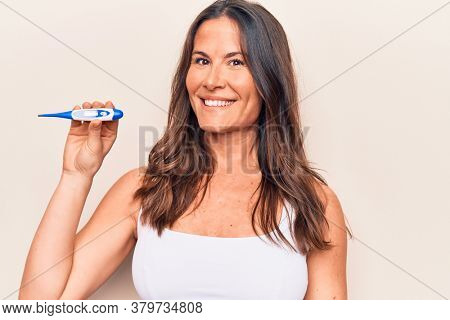 Beautiful brunette woman controlling temperature holding thermometer over white background looking positive and happy standing and smiling with a confident smile showing teeth