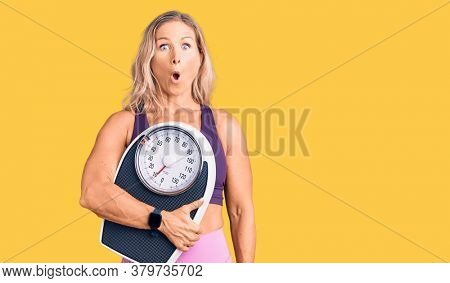 Middle age fit blonde woman wearing sports clothes holding weighing machine scared and amazed with open mouth for surprise, disbelief face
