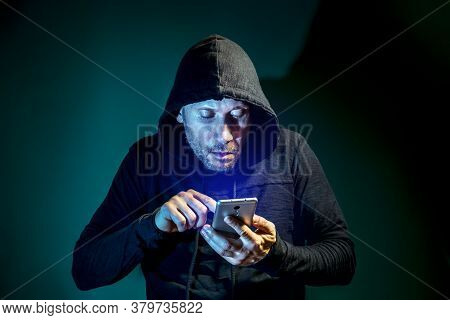 A Male Intruder With A Hood On His Head Searches On A Smartphone On A Dark Green Background