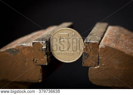 A 5-ruble Coin In A Metal Vise. Concept Of Economic Problems. Selective Focus. Close Up