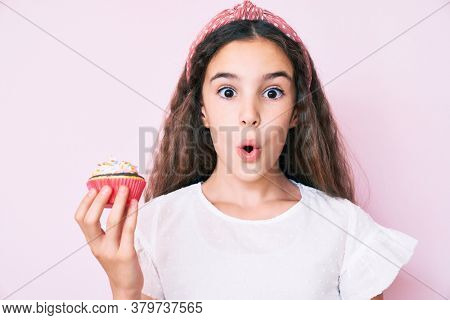 Cute hispanic child girl holding cupcake scared and amazed with open mouth for surprise, disbelief face