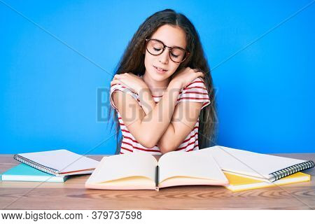 Cute hispanic child girl studying for school exam sitting on the table hugging oneself happy and positive, smiling confident. self love and self care