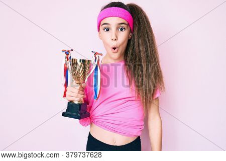 Cute hispanic child girl wearing sportswear holding winner trophy scared and amazed with open mouth for surprise, disbelief face