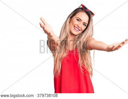 Young beautiful blonde woman wearing sleeveless t-shirt and sunglasses looking at the camera smiling with open arms for hug. cheerful expression embracing happiness.