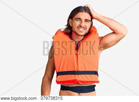Young handsome man wearing nautical lifejacket confuse and wonder about question. uncertain with doubt, thinking with hand on head. pensive concept.