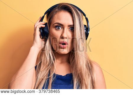 Young beautiful blonde woman listening to music using headphones over yellow background scared and amazed with open mouth for surprise, disbelief face