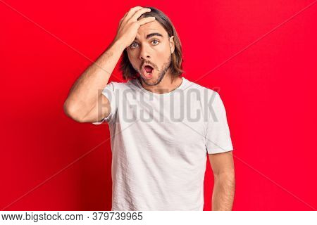 Young handsome man wearing casual clothes surprised with hand on head for mistake, remember error. forgot, bad memory concept.