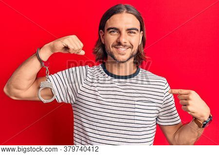 Young handsome man wearing prisoner handcuffs pointing finger to one self smiling happy and proud