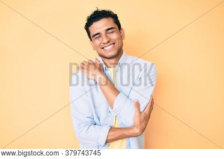 Young handsome hispanic man standing over yellow background hugging oneself happy and positive, smiling confident. self love and self care
