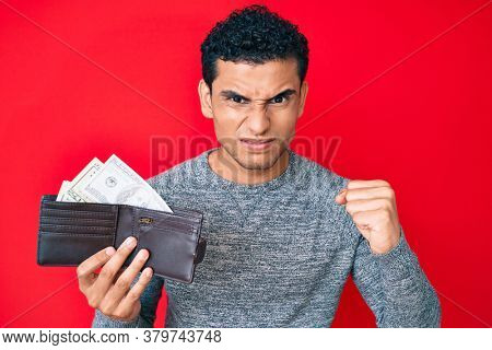 Young handsome hispanic man holding wallet with dollars annoyed and frustrated shouting with anger, yelling crazy with anger and hand raised
