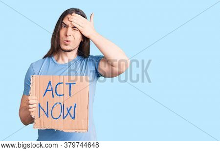 Young adult man with long hair holding act now banner stressed and frustrated with hand on head, surprised and angry face