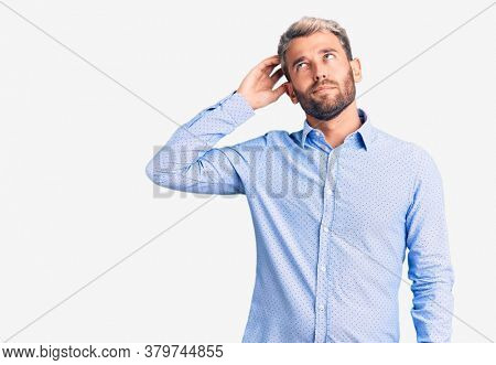 Young handsome blond man wearing elegant shirt confuse and wondering about question. uncertain with doubt, thinking with hand on head. pensive concept.