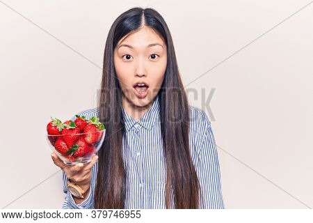 Young beautiful chinese woman holding bowl of strawberries scared and amazed with open mouth for surprise, disbelief face
