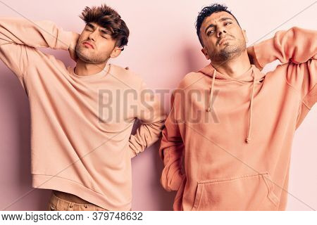 Young gay couple wearing casual clothes suffering of neck ache injury, touching neck with hand, muscular pain