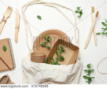 Textile Bag And Disposable Tableware From Brown Craft Paper, Green Mint Leaves On A White Background