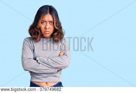 Young beautiful mixed race woman wearing casual clothes skeptic and nervous, disapproving expression on face with crossed arms. negative person.