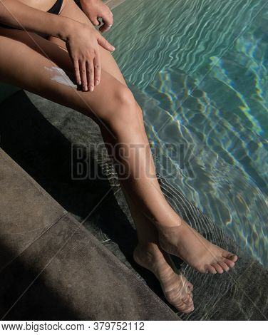Woman Applying Sunscreen Sunblock On Legs Outdoors By Pool Under Sunshine. Summer Skin Care