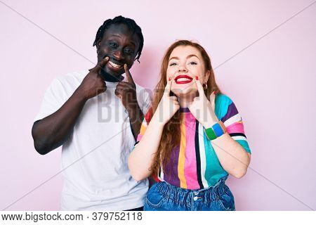 Interracial couple wearing casual clothes smiling with open mouth, fingers pointing and forcing cheerful smile