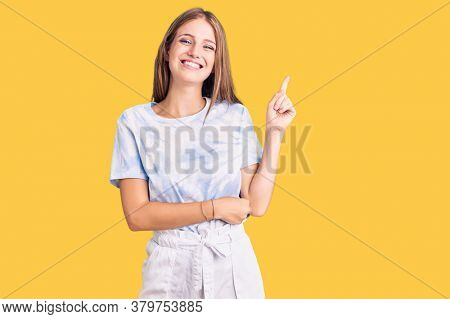 Young beautiful blonde woman wearing tye die tshirt smiling happy pointing with hand and finger to the side