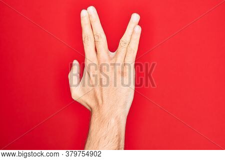 Hand of caucasian young man showing fingers over isolated red background greeting doing Vulcan salute, showing back of the hand and fingers, freak culture