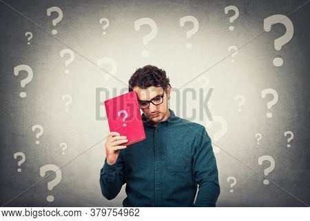 Confused Student Guy Looks Down Upset, Holding A Book With Question Mark And Different Interrogation