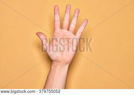 Hand of caucasian young man showing fingers over isolated yellow background counting number 5 showing five fingers