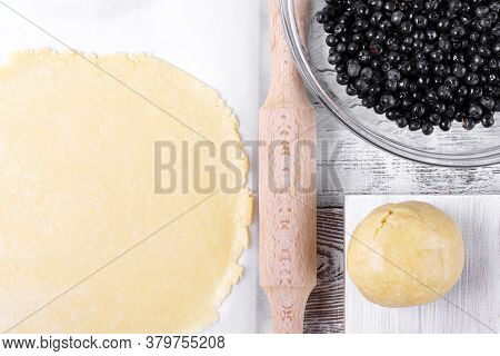 Shortbread Dough And Bilberry On The White Wooden Table. Top View. Ingredients For Making A Pie
