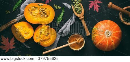 Raw Pumpkin With Herbs, Seeds And Honey On A Black Stone Background, Toned. Autumn Food Background B