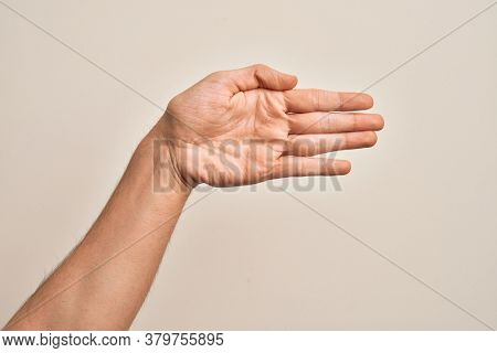 Hand of caucasian young man showing fingers over isolated white background stretching and reaching with open hand for handshake, showing palm