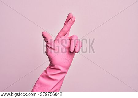 Hand of caucasian young man with cleaning glove over isolated pink background gesturing fingers crossed, superstition and lucky gesture, lucky and hope expression