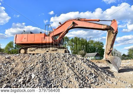 Excavator Work At Landfill With Concrete Demolition Waste. Salvaging And Recycling Building And Cons