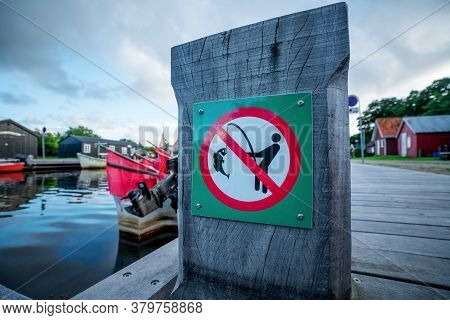 Fishing Prohibited Sign On A Wooden Pier At A Marine Harbor In Cloudy Weather