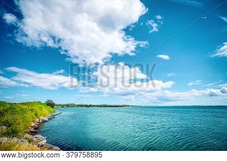 Idyllic Lake With Turquoise Water In The Summer With Rocks By The Lakeside Under A Blue Sky