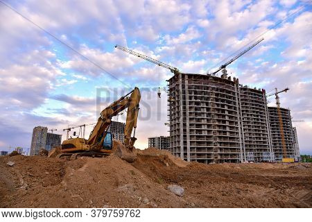 Excavator During Earthmoving At Construction Site On Sunset Background. Backhoe Digs Ground For Unde