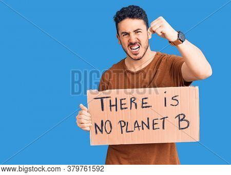 Young hispanic man holding there is no planet b banner annoyed and frustrated shouting with anger, yelling crazy with anger and hand raised