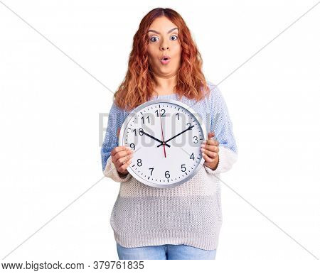 Young latin woman holding big clock scared and amazed with open mouth for surprise, disbelief face