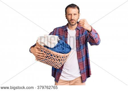 Young handsome man holding laundry basket annoyed and frustrated shouting with anger, yelling crazy with anger and hand raised