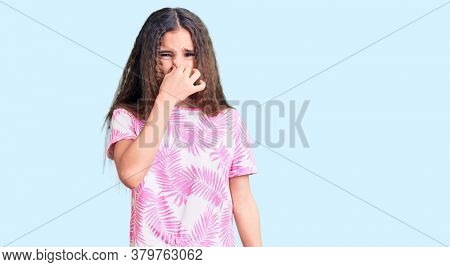 Cute hispanic child girl wearing casual clothes smelling something stinky and disgusting, intolerable smell, holding breath with fingers on nose. bad smell