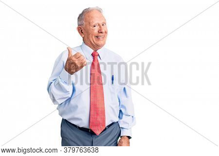 Senior handsome grey-haired man wearing elegant tie and shirt smiling with happy face looking and pointing to the side with thumb up.