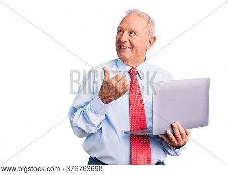 Senior handsome grey-haired man wearing tie using laptop pointing thumb up to the side smiling happy with open mouth